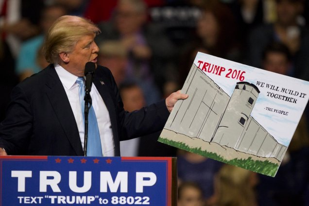 Donald Trump holds a sign from a supporter during a rally Wednesday, March 9, 2016 at the Crown Coliseum in Fayetteville, N.C.